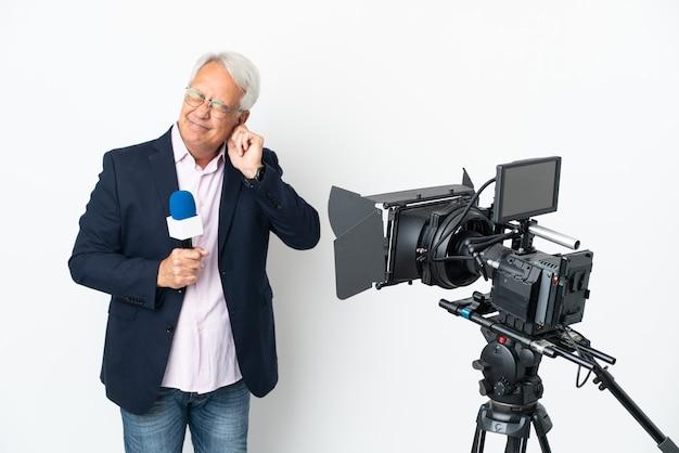 Verslaggever braziliaanse man van middelbare leeftijd die een microfoon vasthoudt en nieuws meldt, geïsoleerd gefrustreerd en oren bedekt