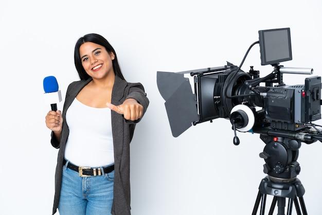 Verslaggever colombiaanse vrouw die een microfoon houdt en nieuws over wit rapporteert dat duimen omhoog gebaar geeft