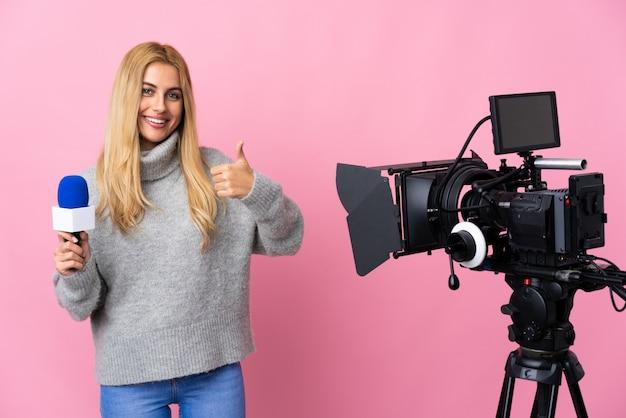 Verslaggever die een microfoon houdt en nieuws over geïsoleerde roze muur rapporteert die copyspace denkbeeldig op de palm houdt om een advertentie in te voegen en met duimen omhoog