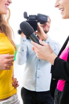 Verslaggever en cameraman schieten een interview