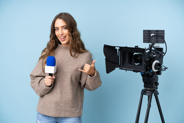 Verslaggever jonge vrouw die een microfoon houdt en nieuws rapporteert dat telefoongebaar maakt