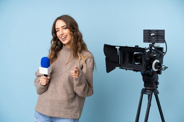 Verslaggever jonge vrouw met een microfoon en rapportage nieuws punten vinger naar je