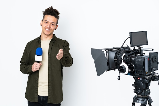 Verslaggever man met een microfoon en nieuws handshaking rapporteren na goede deal