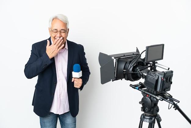 Verslaggever middelbare leeftijd braziliaanse man met een microfoon en rapportage van nieuws geïsoleerd op witte achtergrond gelukkig en lachend die mond met de hand bedekken