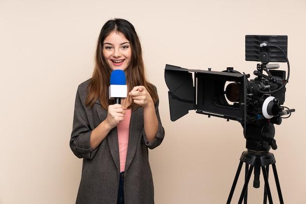 Verslaggever vrouw houdt een microfoon en rapporteert nieuws over muur wijst vinger naar je