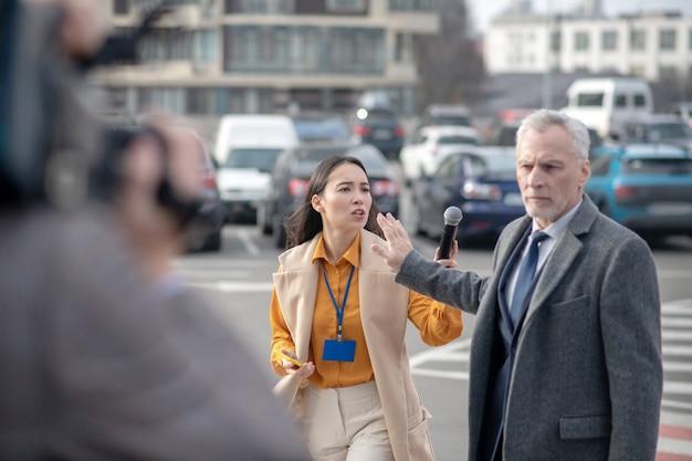 Verslaggevers die met een videocamera proberen te praten met een beroemde zakenman naast zijn kantoor