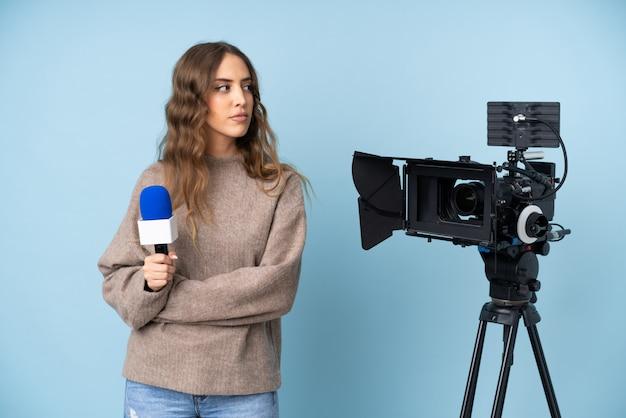 Verslaggevers jonge vrouw die een microfoon houden en nieuws melden die kant kijken