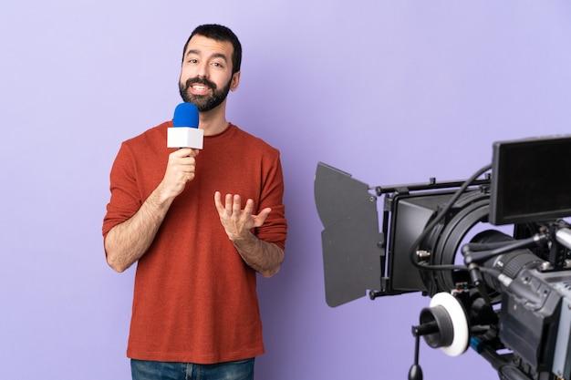 Verslaggeversmens die een microfoon houdt en nieuws over geïsoleerde purpere muur rapporteert