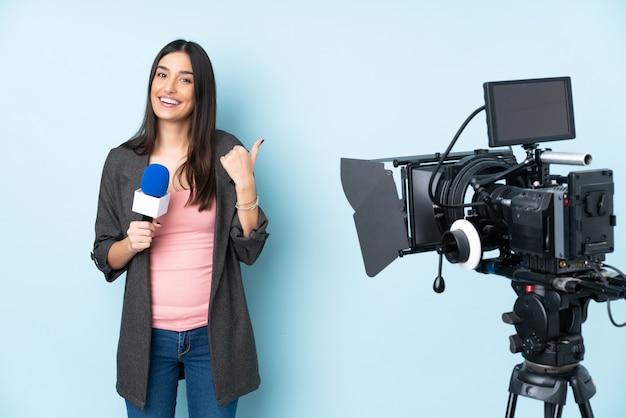 Verslaggeversvrouw die een microfoon houden en nieuws melden dat op blauwe muur met duimen op gebaar en het glimlachen wordt geïsoleerd