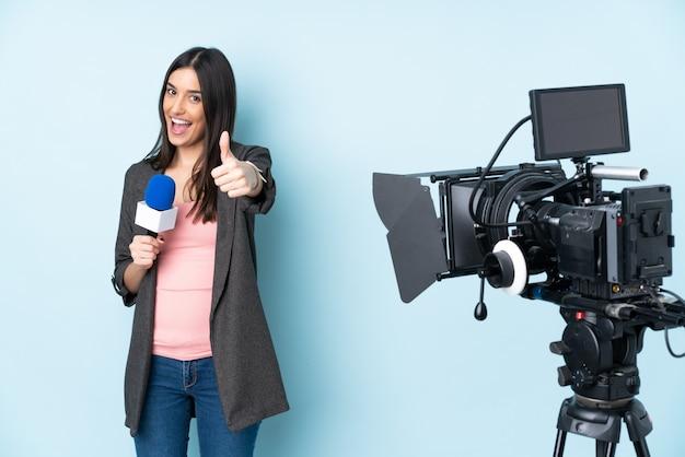 Verslaggeversvrouw die een microfoon houden en nieuws melden dat op blauwe muur met omhoog duimen wordt geïsoleerd omdat er iets goeds is gebeurd