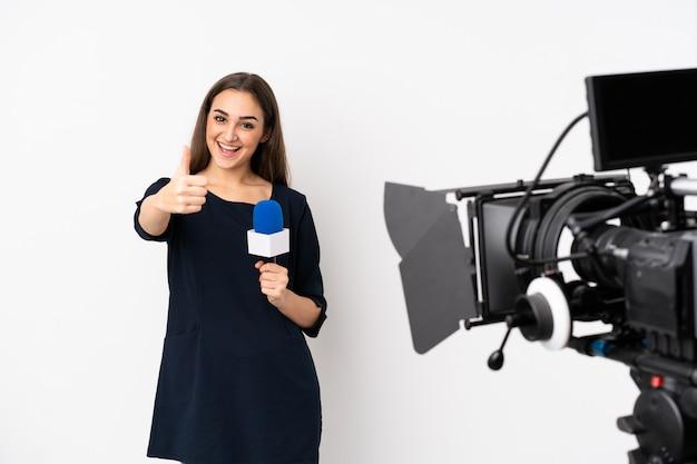 Verslaggeversvrouw die een microfoon houden en nieuws melden dat op witte muur met omhoog duimen wordt geïsoleerd omdat er iets goeds is gebeurd
