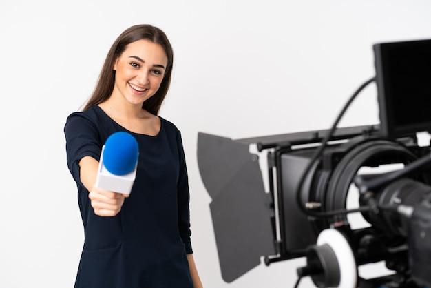 Verslaggeversvrouw die een microfoon houden en nieuws melden dat op witte muur wordt geïsoleerd