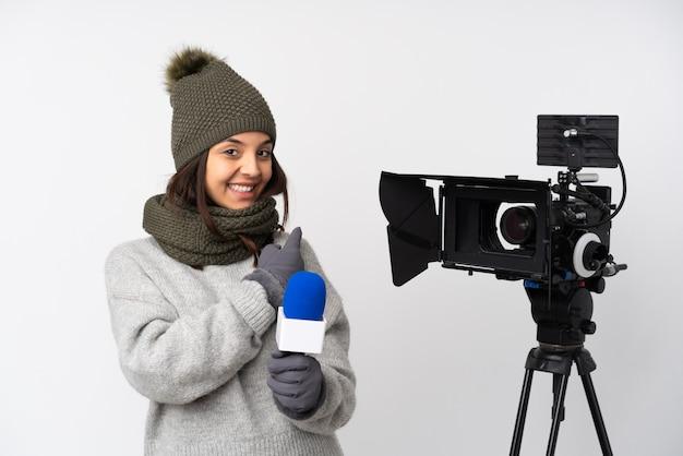 Verslaggeversvrouw die een microfoon houden en nieuws melden over geïsoleerde witte muur die terug richt
