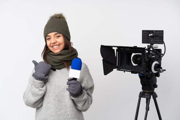 Verslaggeversvrouw die een microfoon houden en nieuws met duimen op gebaar en het glimlachen melden