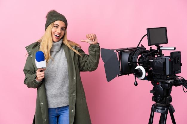 Verslaggeversvrouw die een microfoon houden en nieuws over geïsoleerd roze rapporteren die duimen omhoog gebaar geven
