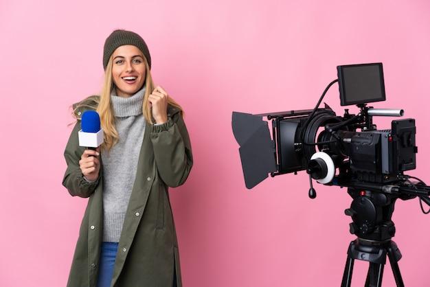 Verslaggeversvrouw die een microfoon houden en nieuws over het geïsoleerde roze muur lachen rapporteren