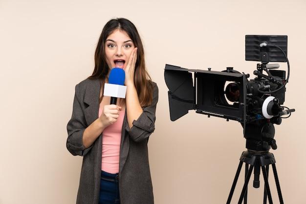 Verslaggeversvrouw die een microfoon houden en nieuws over muur met verraste gelaatsuitdrukking rapporteren