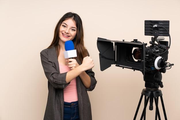 Verslaggeversvrouw die een microfoon houden en nieuws over muur rapporteren die een overwinning vieren