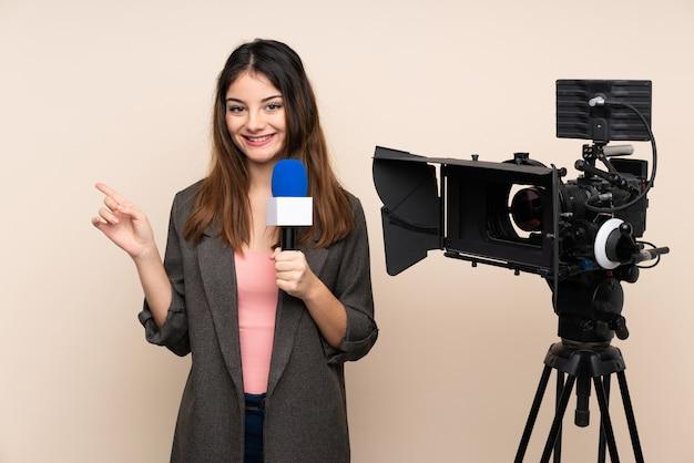 Verslaggeversvrouw die een microfoon houden en nieuws over muur rapporteren die vinger aan de kant richten
