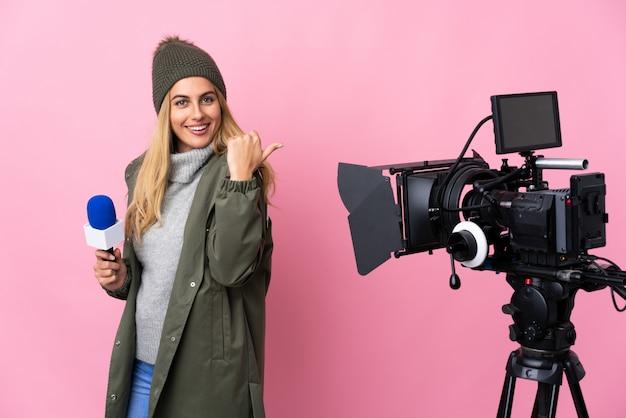 Verslaggeversvrouw die een microfoon houden en nieuws over roze muur met duimen op gebaar en het glimlachen rapporteren
