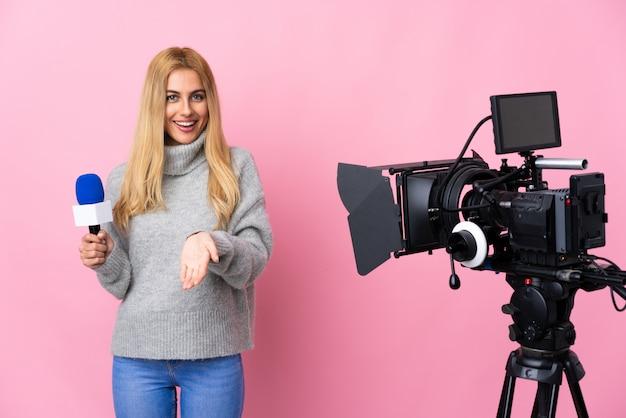 Verslaggeversvrouw die een microfoon houden en nieuws over roze muur met verrassing en geschokte gelaatsuitdrukking rapporteren