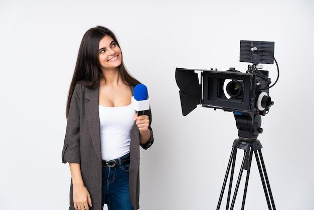 Verslaggeversvrouw die een microfoon houden en nieuws over witte en muur melden die omhoog lachen