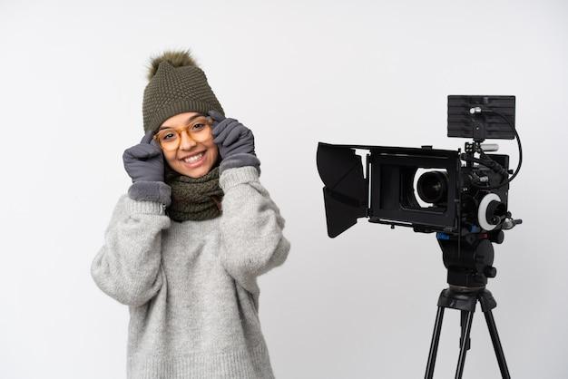 Verslaggeversvrouw die een microfoon houden en nieuws over witte muur met glazen melden en gelukkig