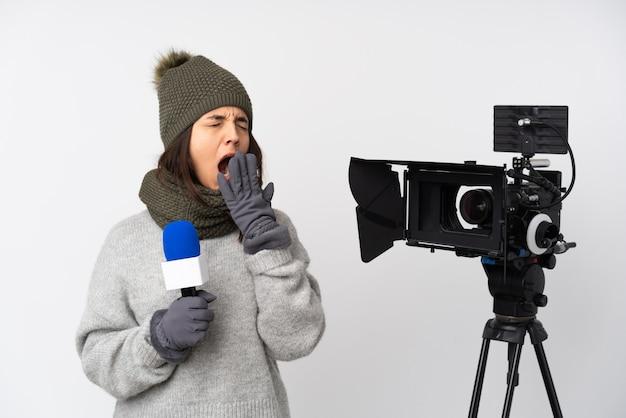 Verslaggeversvrouw die een microfoon houden en nieuws over witte muur rapporteren die en wijd open mond met hand geeuwen