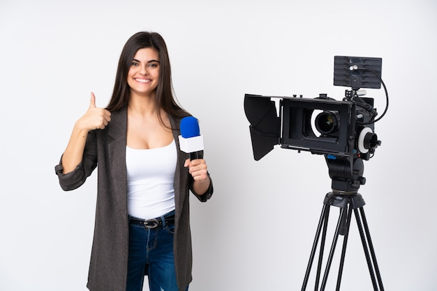 Verslaggeversvrouw die een microfoon houden en nieuws over witte muur rapporteren duimen op gebaar geven