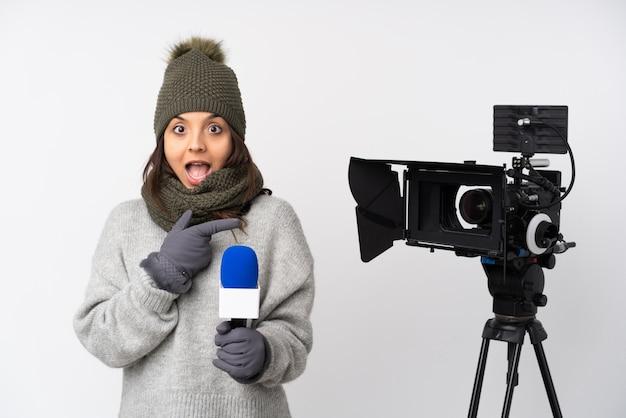 Verslaggeversvrouw die een microfoon houdt en nieuws over witte muur verrast verrast en vinger aan de kant richt