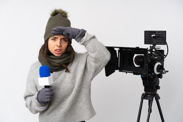 Verslaggevervrouw die een microfoon houdt en nieuws rapporteert over geïsoleerde witte muur die ver weg met hand kijkt om iets te kijken