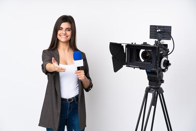 Verslaggevervrouw die een microfoon houdt en nieuws rapporteert over geïsoleerde witte muurhandshaking na goede overeenkomst