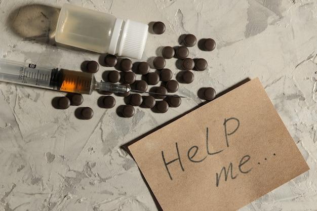Verslavende medicijnen. lsd, cocaïne, heroïne en het opschrift helpen me een heldere tafel. het concept van drugsverslaving. uitzicht van boven.