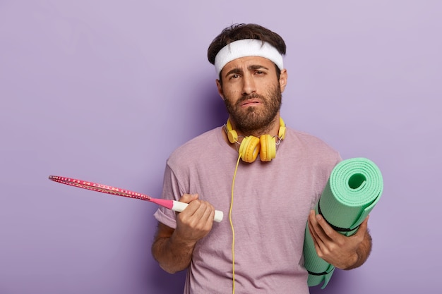 Versleten actieve man poseren met sportartikelen