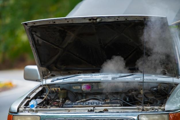 Versleten auto met rokende motor, oververhitte motor op de weg.