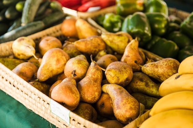 Versleten peer in rieten mand voor verkoop bij fruitmarkt