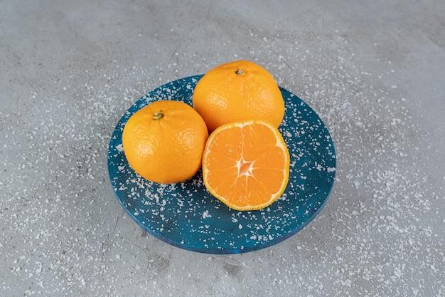 Versleten schaal bedekt met kokospoeder met sinaasappels op marmeren oppervlak