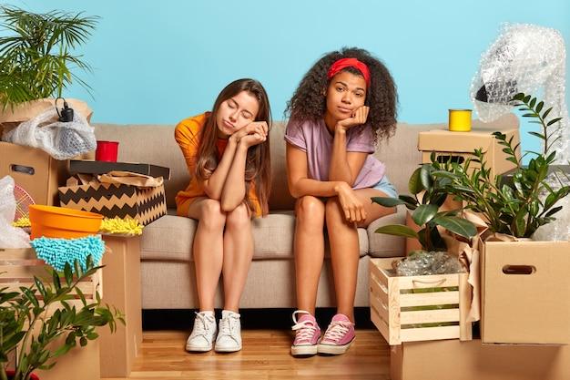 Versleten, uitgeputte zussen nemen op de verhuisdag pauze nadat ze dingen uit dozen hebben gehaald
