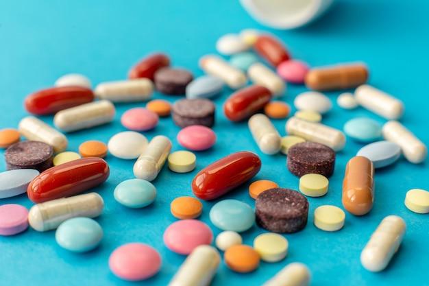 Verspreid handvol gekleurde pillen op blauw