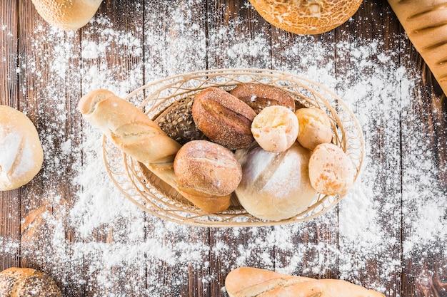 Verspreid meel over de broodmand op de houten tafel