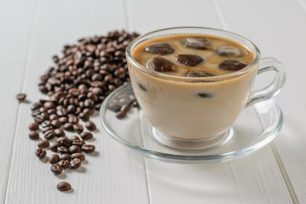 Verspreid op een witte tafel koffiebonen en een kopje ijs koffie op een witte houten tafel. verfrissende en verkwikkende drank van koffiebonen en melk.