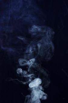 Verspreid witte rook op zwarte achtergrond