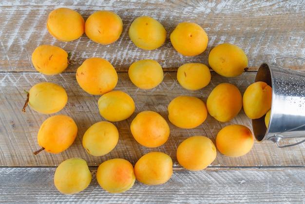Verspreide abrikozen uit mini-emmer op een houten tafel. plat lag.