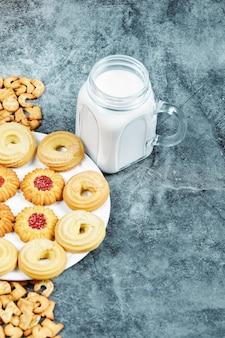 Verspreide alfabetcrackers, een bord met koekjes en een potje melk op marmeren tafel.