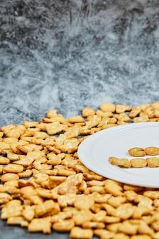 Verspreide alfabetcrackers en woord goedemorgen gespeld met crackers op een witte plaat.