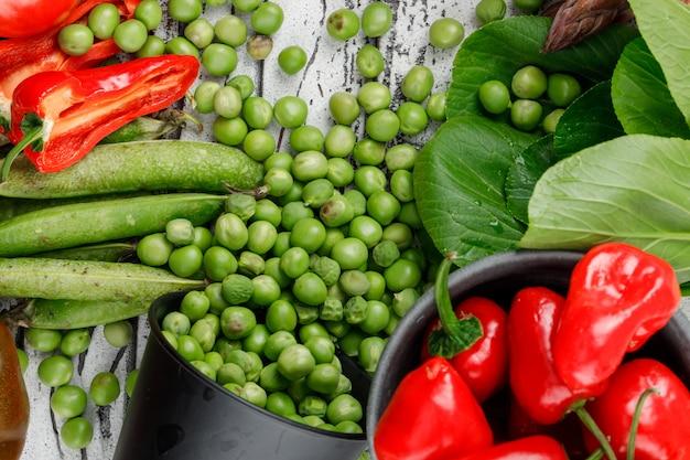 Verspreide erwten uit een emmer met pepers, paksoi, groene peulen close-up op een houten muur