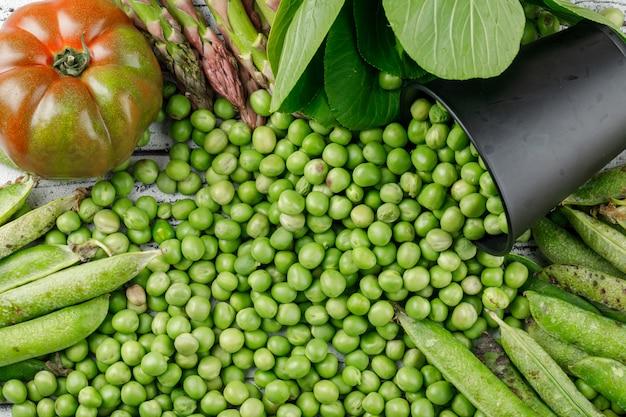 Verspreide erwten uit een mini-emmer met paksoi, groene peulen, tomaat, asperges plat op een houten muur