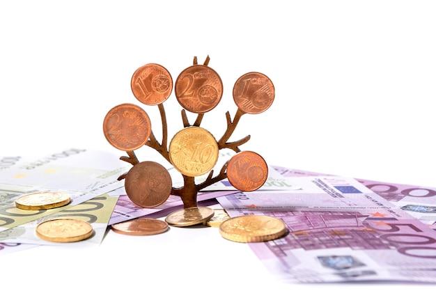 Verspreide eurobiljetten op een witte achtergrond en een groeiende boom met munten op de takken close-up. investeringsconcept geldgroei.