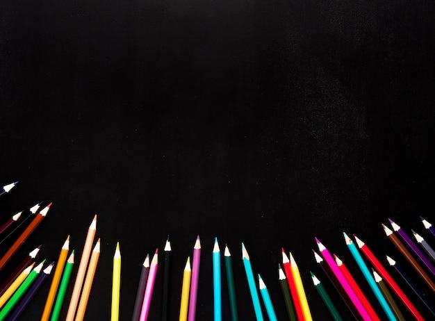 Verspreide gescherpte kleurenpotloden die op bodem van zwarte achtergrond worden geplaatst