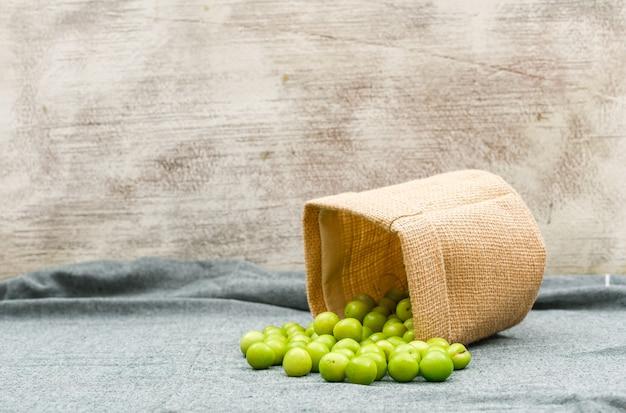 Verspreide groene pruimen in een open canvas zak op grunge oppervlak en picknick doek, zijaanzicht.